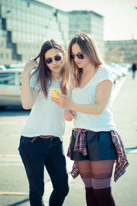 two beautiful young women using smart phone in the city
