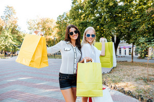 Two beautiful young women with shopping bags walking in the ctiy