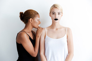 Two beautiful young women with stylish makeup standing and posing over white background