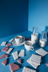 Two bottles with milk, cups and broken cookies over blue background
