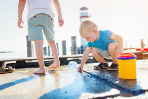 Two boys playing on the pier at the lighthouse on sunny summer day