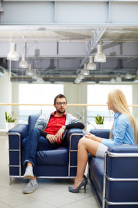 Two business people interacting while sitting in office