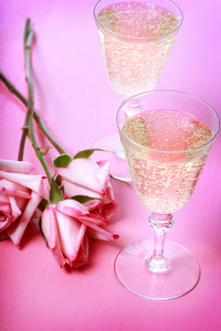 Two champagne glasses with pink roses on pink table