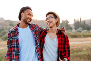 Two cheerful asian and african american young friends standing together outdoors