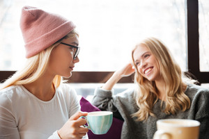 Two cheerful charming young women drinking coffee and talking in cafe