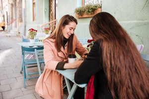 Two cheerful cute young women drinking coffe and lauging in outdoor cafe