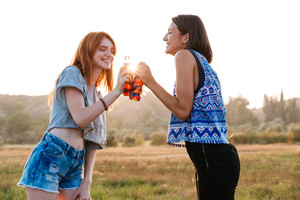 Two cheerful cute young women drinking soda and having fun outdoors