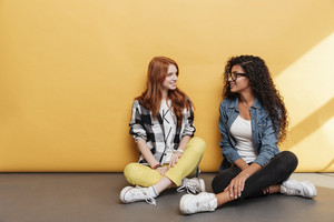 Two cheerful cute young women sitting and talking over yellow background