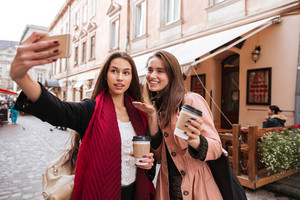 Two cheerful lovely young women making selfie with cell phone in old city