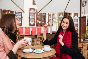 Two cheerful lovely young women smiling and drinking coffe with french macaroons in outdoor cafe