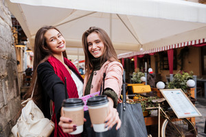 Two cheerful lovely young women standing and holding takeaway coffee in old town