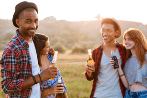 Two cheerful multiethnic couples drinking beer and soda outdoors