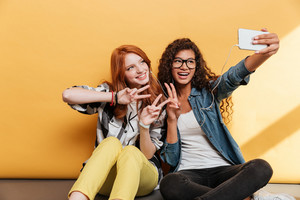 Two cheerful pretty young women listening to music and taking selfie over yellow background