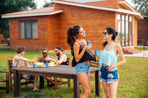 Two cheerful pretty young women talking and laughing on summer outdoor party