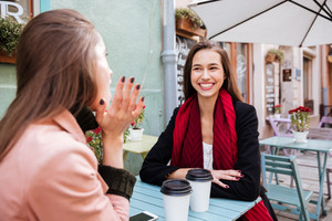 Two cheerful pretty young women talking and lauging in outdoor cafe