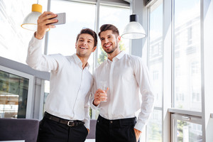 Two cheerful young businessmen standing and taking selfie in office