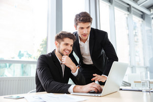 Two cheerful young businessmen working and using laptop on business meeting together