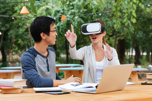 Two cheerful young students studying and using virtual reality glasses outdoors
