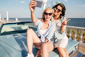 Two cheerful young women sitting on car and taking selfie with mobile phone