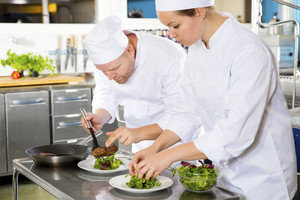 Two chefs prepares steak dish at gourmet restaurant