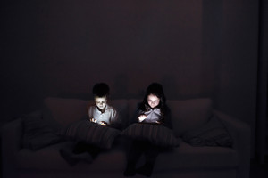 Two children playing with gadgets, sitting on sofa in dark room at night.