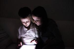 Two children playing with tablet, sitting on sofa in dark room at night.
