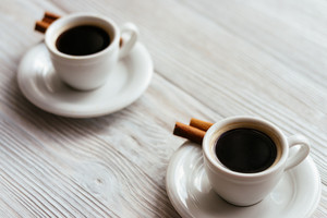 Two cups of espresso with cinnamon sticks on a white wooden table.