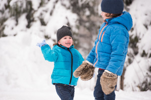 Two cute boys in blue jackets, hats and gloves playing outside in winter nature, throwing snow balls