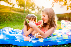 Two cute girls eating watermelon outside in garden, lying on inflatable mat, sunny summer back yard