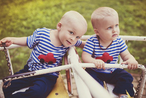 Two cute little boys on an old carousel.