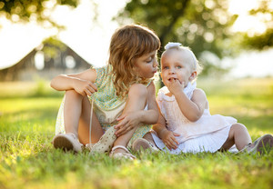 Two cute little sisters laughing and playing in green sunny park