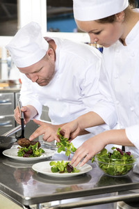 Two dedicated chefs prepares steak dish at gourmet restaurant