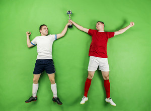 Two football players celebrating victory. Studio shot on a green background.