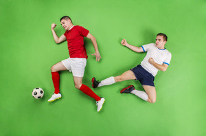 Two football players fighting for a ball. Studio shot on a green backgroud.