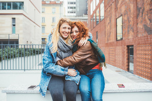 Two friends redhead and blonde girl in the street of the city hugging , looking in camera, smiling –friendship, happiness concept