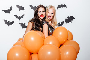 Two frightening young women with halloween makeup holding orange balloons and showing teeth over white background