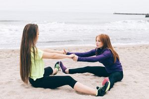 Two girls in sportswear doing stretching on a beach, concept of healthy lifestyle