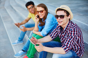 Two guys with touchpads and girl with cellphone spending leisure outdoors