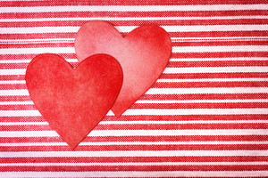 Two handcrafted paper hearts on red and white striped background