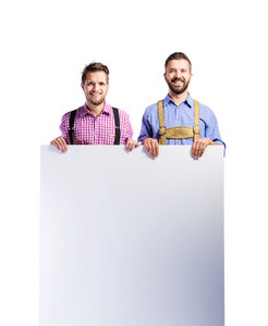 Two handsome hipster young men in traditional bavarian clothes holding empty white board, copy space. Oktoberfest. Studio shot on white background, isolated.
