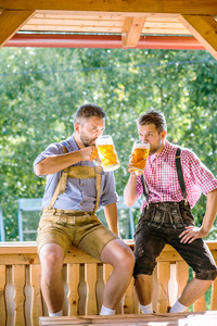 Two handsome hipster young men in traditional bavarian clothes holding mugs of beer. Oktoberfest. Sunny summer garden.