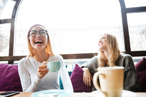 Two happy attractive young women drinking coffee and laughing in cafe