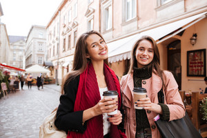 Two happy attractive young women with coffee to go walking and talking in old town