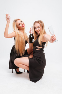 Two happy beautiful young women celebrating and drinking champagne over white background