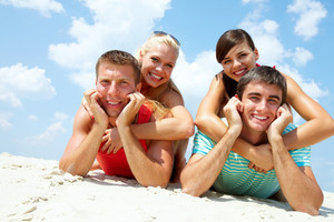 Two happy couples lying on sand and looking at camera