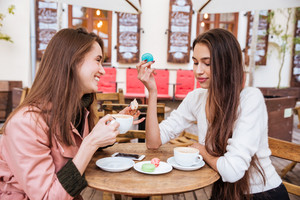 Two happy cute young women drinking coffee and eating french macaroons in outdoor cafe