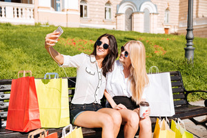 Two happy friends taking selfie while resting on the bench after shopping