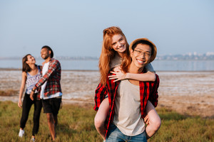 Two happy multiethnic young couples having fun outdoors