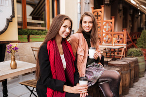 Two happy pretty young women sitting and drinking coffee in old city