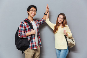 Two happy smiling interracial students standing with backpacks and giving high five isolated on the gray background